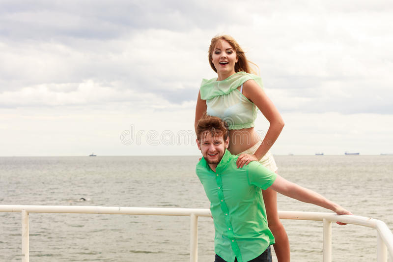 Couple in love having fun on sea pier. Summer happiness concept. Woman and men young couple in love playing sharing free time having fun outdoor on sea pier sky stock photos