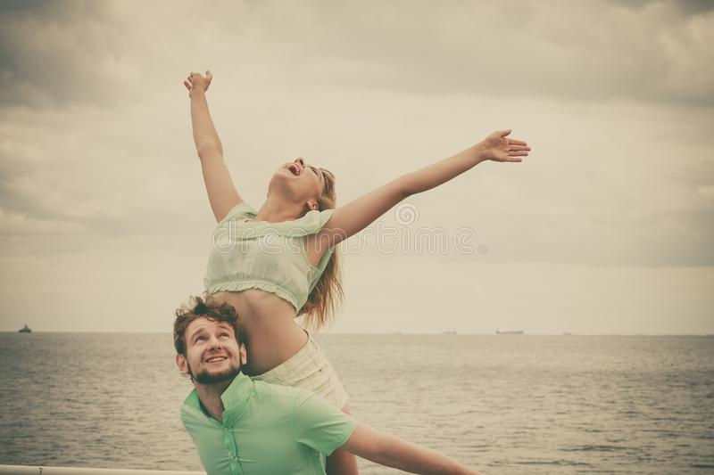 Couple in love having fun on sea pier. Summer happiness concept. Woman and men young couple in love playing sharing free time having fun outdoor on sea pier sky royalty free stock photography