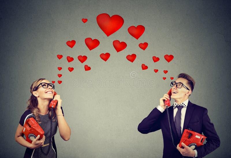 Couple in love having romantic telephone conversation. Young cute couple in love having romantic telephone conversation with red hearts on background stock images