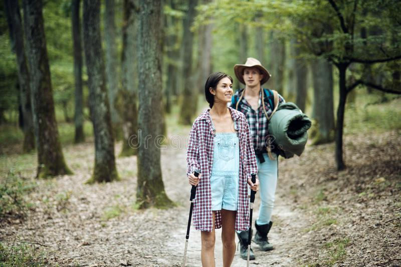 Couple in love hiking in forest with touristic equipment royalty free stock photography