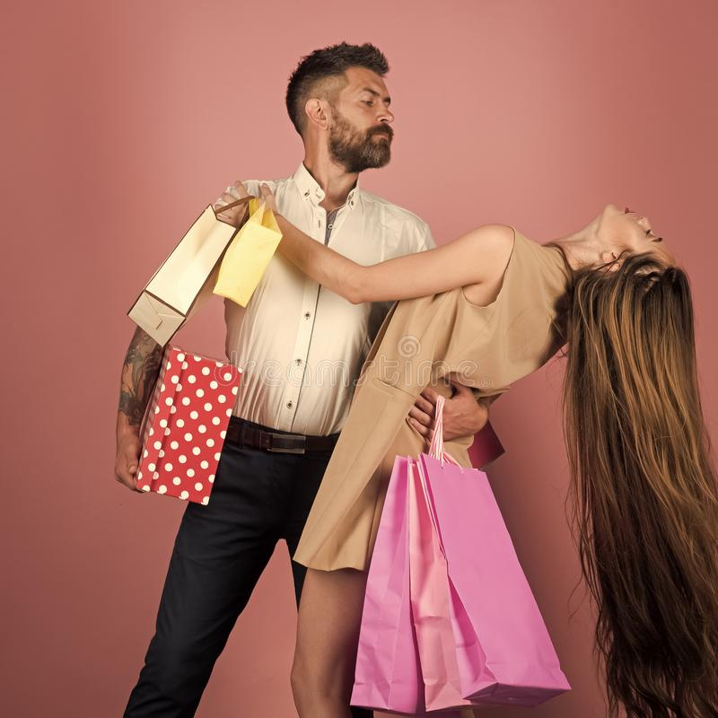 Couple in love hold shopping bag near pink wall. royalty free stock photo