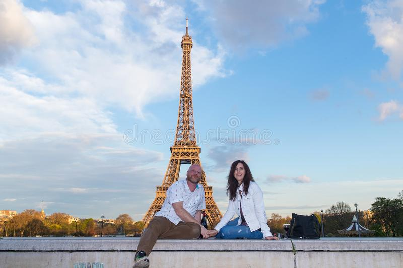 Couple in love holding hands at the Eiffel Tower in Paris, Franc. A men and a women enjoy a bottle of red wine near the Eiffel Tower in Paris, France royalty free stock images