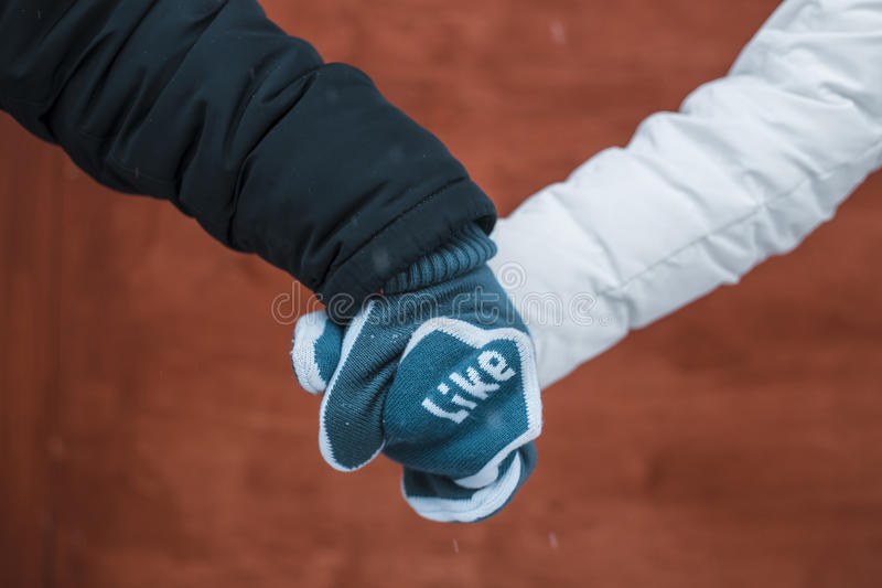 Couple in love holding hands in mittens royalty free stock image