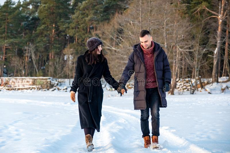 Couple in love holding hands and walking together in park in winter royalty free stock photos