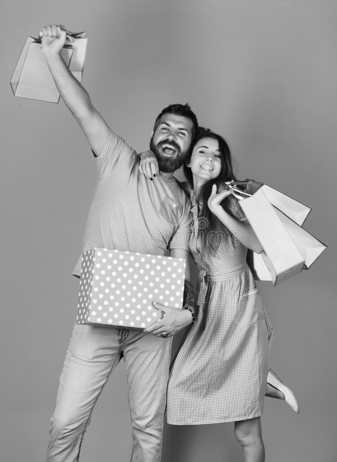 Couple in love holds shopping bags on yellow background. Man with beard holds red polka dotted box royalty free stock image