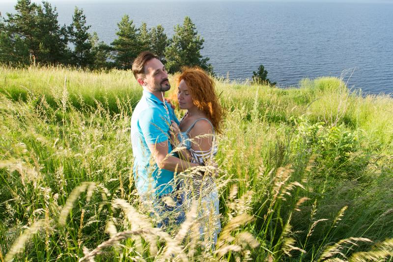 couple in love hugging in big green grass. Couple in love passionately hugging. Long-awaited meeting of the two lovers in grass royalty free stock photo