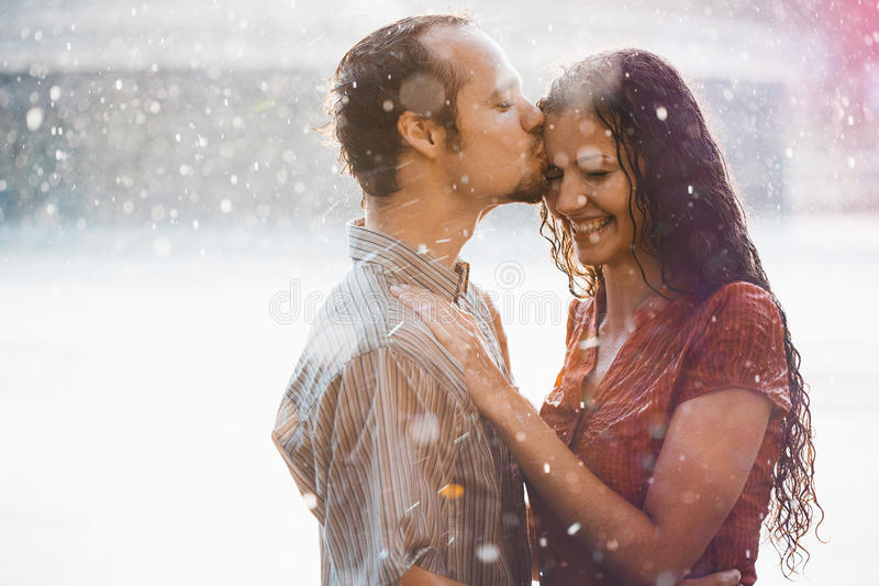 Couple in love hugging and kissing. Under summer rain stock photography