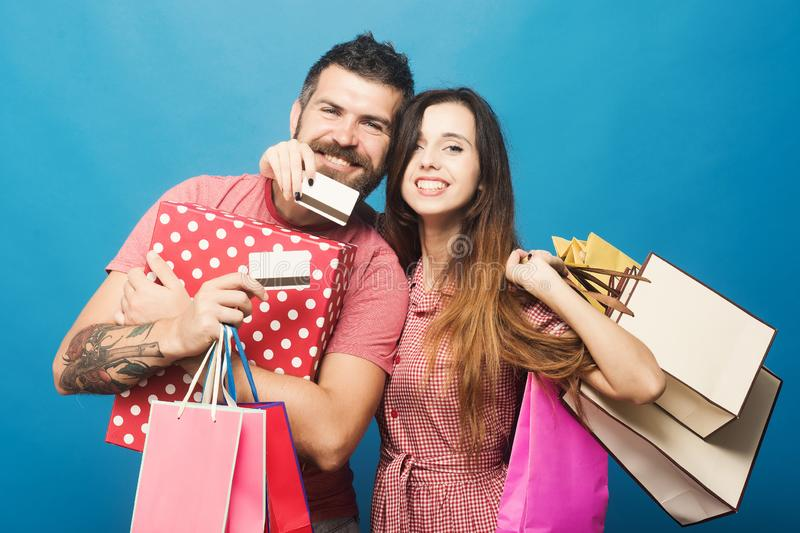 Couple in love hugs holding shopping bags and credit cards stock photo