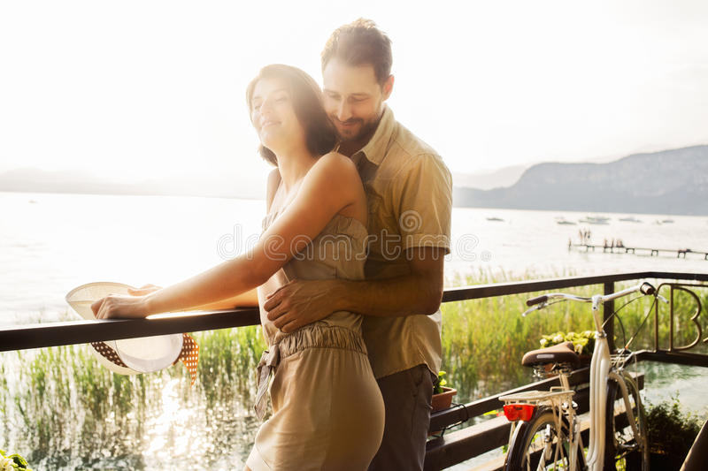 Couple in love joking in a terrace on the lake royalty free stock image