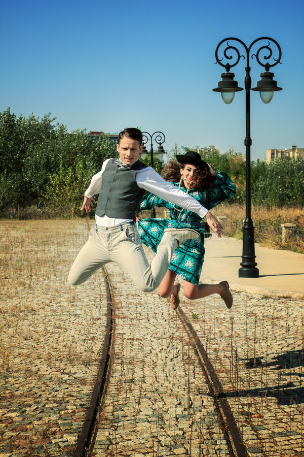 couple in love jumping in air high in middle of the street in old vintage town stock photo