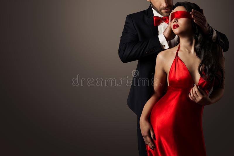 Couple Love Kiss, Man and Blindfolded Woman in Red Dress. Couple Love Kiss, Blindfolded Woman Dancing in Red Dress and Elegant Man in Suit stock photo