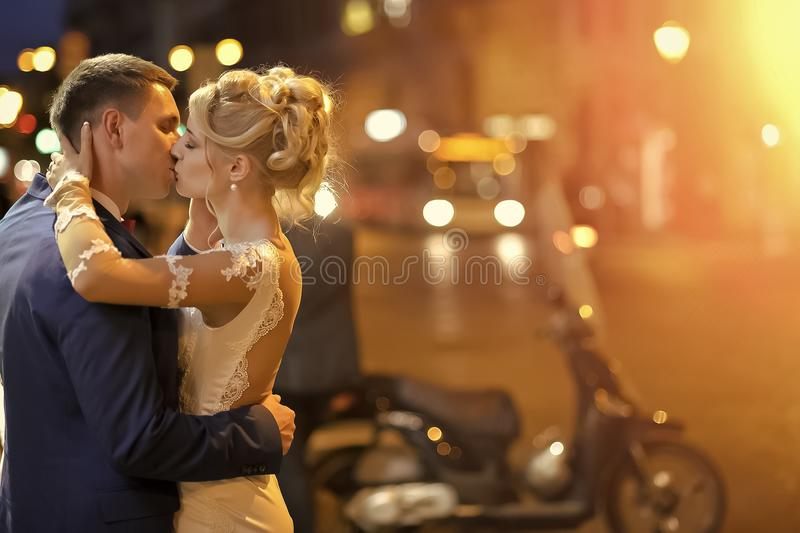 Couple in love kisses. Wedding couple at night city street. Couple in love kisses. Lovely young wedding couple of blond woman in white dress and man in blue suit stock image