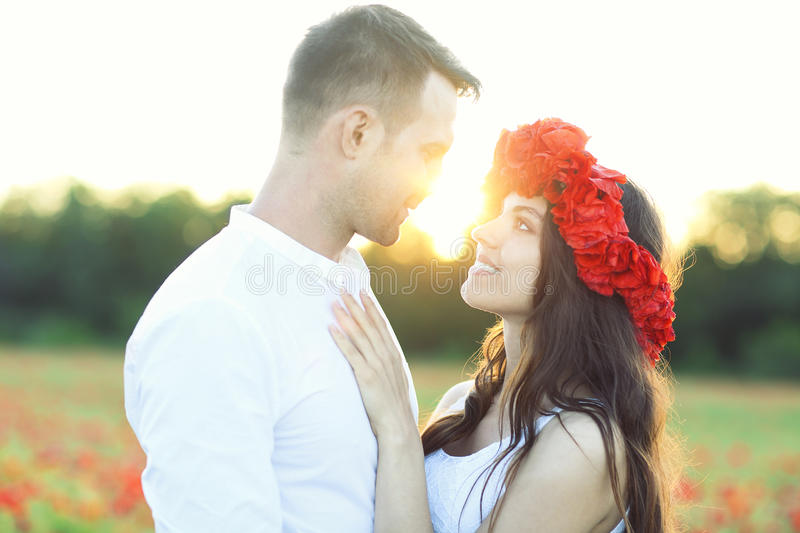 Couple in love kissing and hugging at poppy field royalty free stock photography