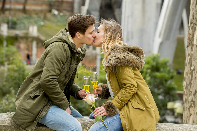 Couple in love kissing tenderly on street celebrating Valentines day or anniversary cheering in Champagne royalty free stock photos