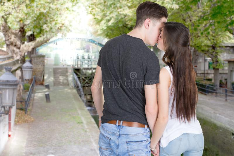 Couple in love in lifestyle are kissing at the edge of the canal river of the city stock photo