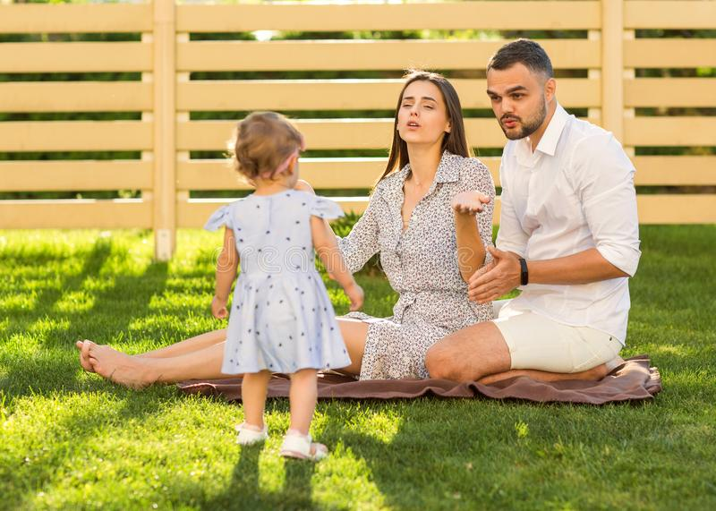 couple in love with little daughter on a picnic near their home, American style. stock photography