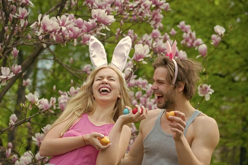 Couple in love in magnolia flower, spring. family. Couple in love of sensual women and men with easter eggs stock image
