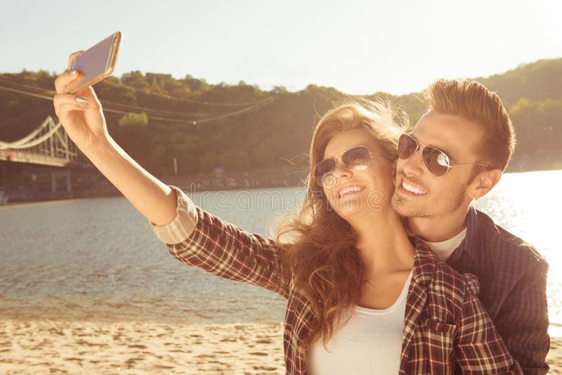 Couple in love making selfie photo on the beach stock photography