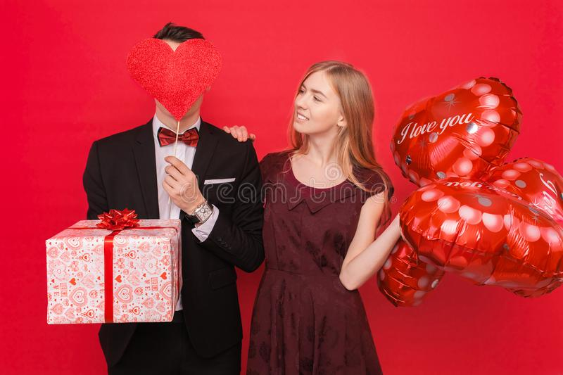 Couple in love, man and woman give each other gifts, holding gift boxes and balloons, on a red background Valentine`s Day concept. Couple in love, men and women stock images