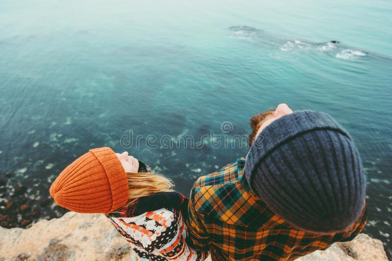 Couple in love Man and Woman together above sea on cliff looking up Traveling happy emotions Lifestyle concept. Young family at ro stock images