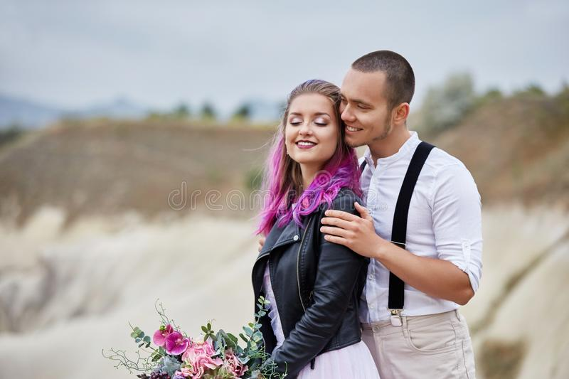 Couple in love meets the dawn in nature, a man and a woman hugging and kissing. Beautiful couple romantic walk, close relationship. Couple in love meets the dawn royalty free stock images