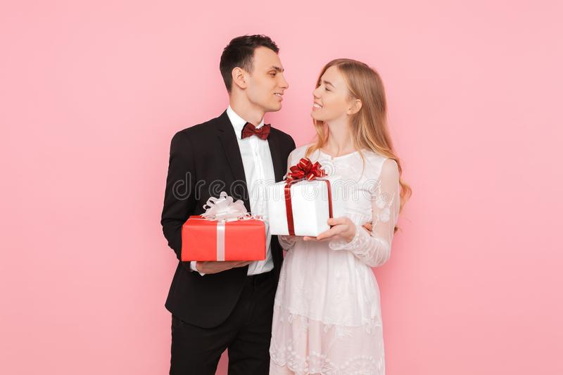 Couple in love, man and woman give each other gifts, on pink background, valentines day concept. Couple in love, men and women give each other gifts, on pink stock photos