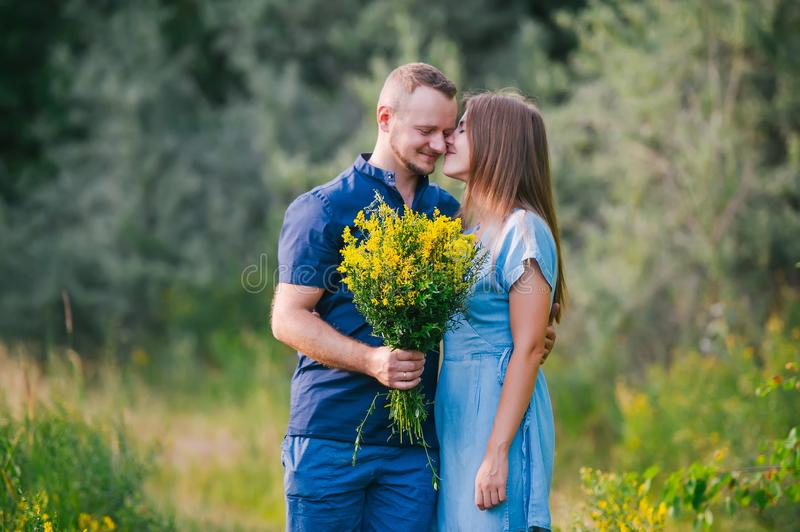 Couple in love on nature with a bouquet of wild yellow flowers. Closeup portrait royalty free stock photography