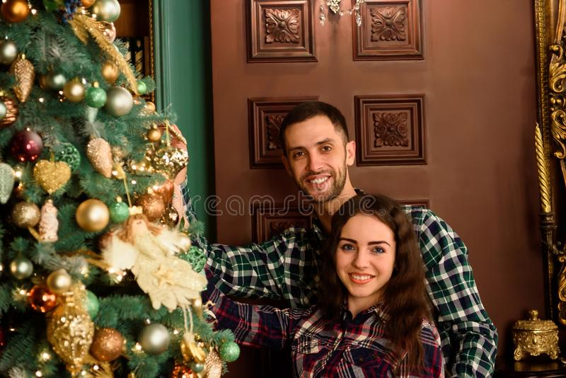 Couple in love next to a Christmas tree, hugging and looking to the camera stock photography