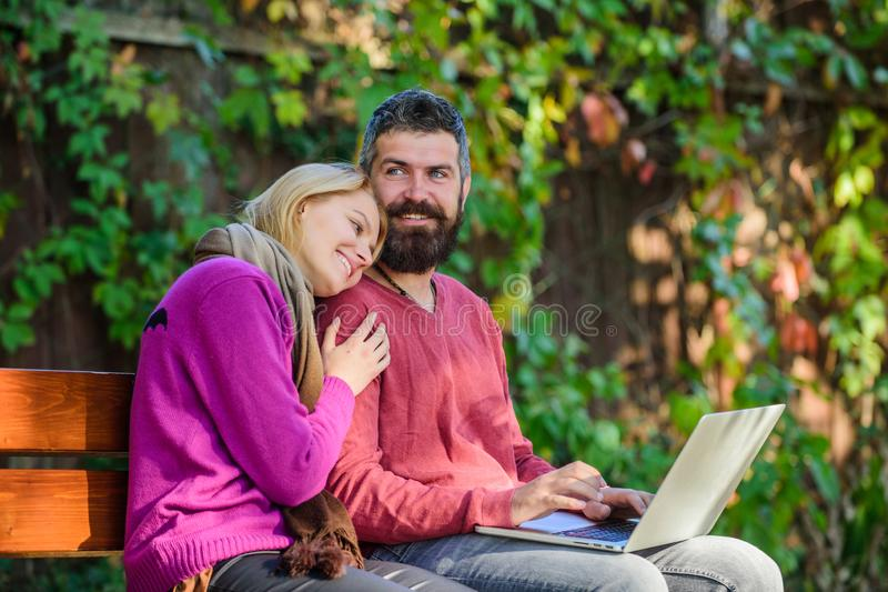 Couple in love notebook consume content. Internet surfing concept. Couple with laptop sit bench in park nature. Background. Surfing internet together. Family royalty free stock photos