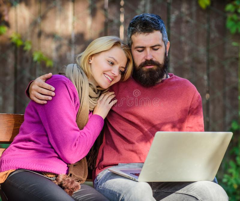 Couple in love notebook consume content. Couple with laptop sit bench in park nature background. Surfing internet. Together. Family surfing internet for royalty free stock photography