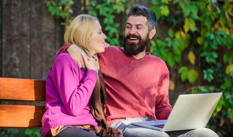 Couple in love notebook consume content. Surfing internet together. Couple with laptop sit bench in park nature. Background. Family surfing internet for stock photo