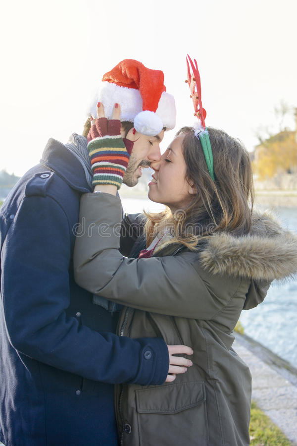 Couple in love outdoors with Christmas hats. Couple in love standing outdoors with Christmas hats royalty free stock image