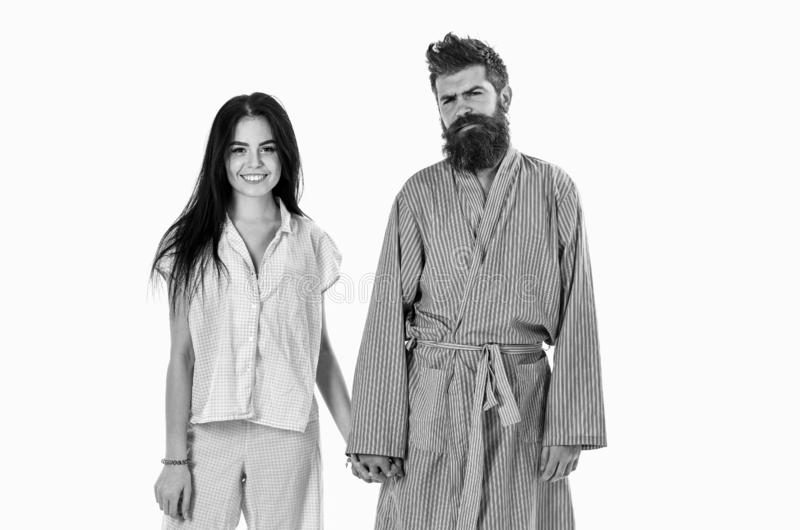 Couple in love in pajama, bathrobe. Couple, family on smiling faces in clothes for sleep looks sleepy in morning. Couple. Hold hands together, isolated on white stock image
