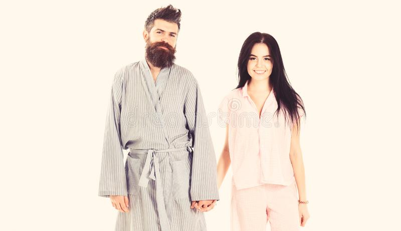 Couple in love in pajama, bathrobe. Couple, family on smiling faces in clothes for sleep looks sleepy in morning. Wake. Up and morning concept. Couple hold stock photography
