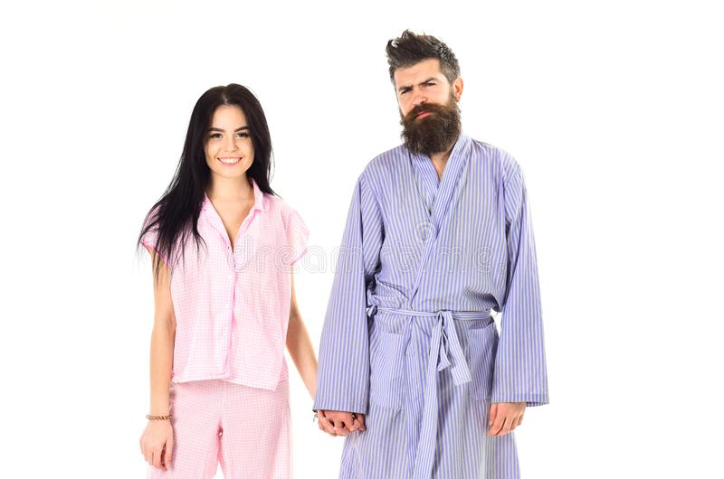Couple in love in pajama, bathrobe. Couple, family on smiling faces in clothes for sleep looks sleepy in morning. Couple. Hold hands together, isolated on white stock photography
