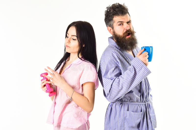 Couple in love in pajama, bathrobe stand back to back. Girl with dumbbell, man with coffee cup, isolated on white stock images