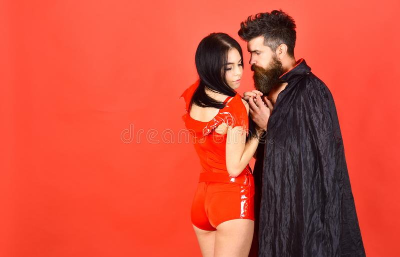 Couple in love, perfect match. Vampire in cloak and devil girl holds hands. Couple on pensive faces play role game. Devil love concept. Man and women dressed royalty free stock image