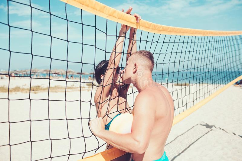 Couple in love play volleyball on sunny beach. Summer vacation and travel on holiday in Miami. Love and flirting of. Couple. women and muscular men with ball at stock photos