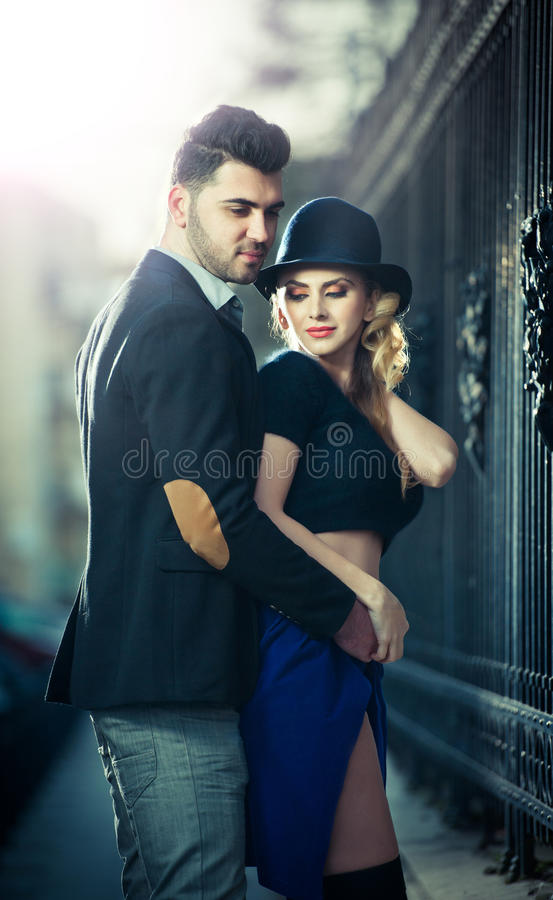 Couple in love in railway station. Beautiful well-dressed couple standing on railway platform. Handsome brunette young men holding a fashionable blonde with royalty free stock photos