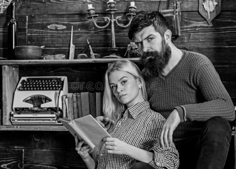Couple in love reading poetry in warm atmosphere. Lady and man with beard on dreamy faces with book, reading romantic royalty free stock photography