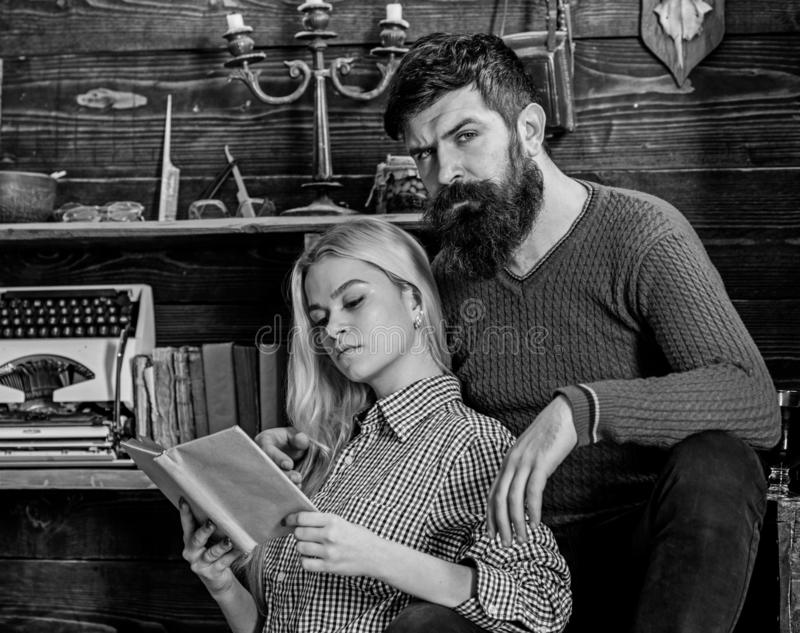 Couple in love reading poetry in warm atmosphere. Lady and man with beard on dreamy faces with book, reading romantic royalty free stock photos