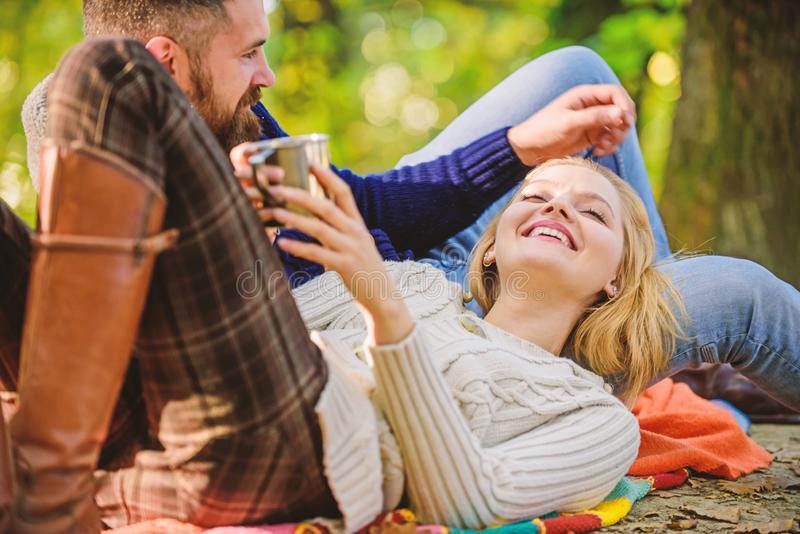 Couple in love relax in autumn forest with tea or coffee. happy woman and bearded man drink mulled wine. love date and royalty free stock photography