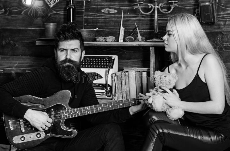 Couple in love on relaxed faces enjoy romantic atmosphere. Man play guitar while lady holds teddy bear in hands royalty free stock image