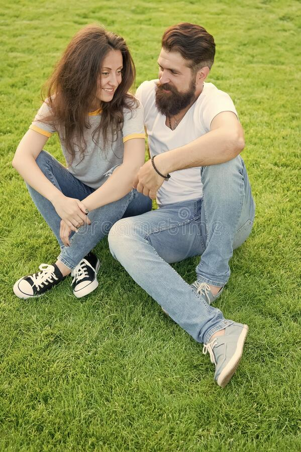 Couple in love relaxing on green lawn. Lovely couple outdoors. Simple happiness. Couple relations goals. Couple spend stock photography