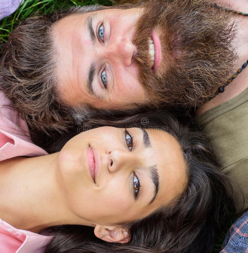 Couple in love relaxing lay at meadow close up. Hipster bearded man and girl happy carefree enjoy relax. Man unshaven royalty free stock images