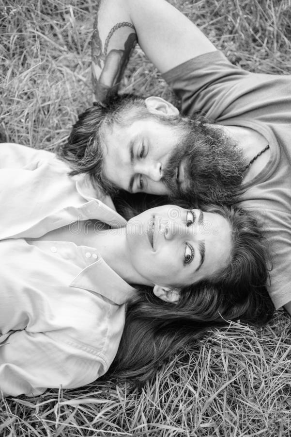 Couple in love relaxing lay at meadow. Nature fills them freshness and peace. Hipster bearded man and girl happy stock photos