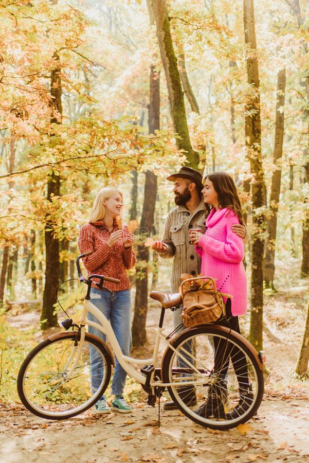 Couple in love ride bicycle together in forest park. Friends with bicycle. Bearded man and women relaxing in autumn stock photo