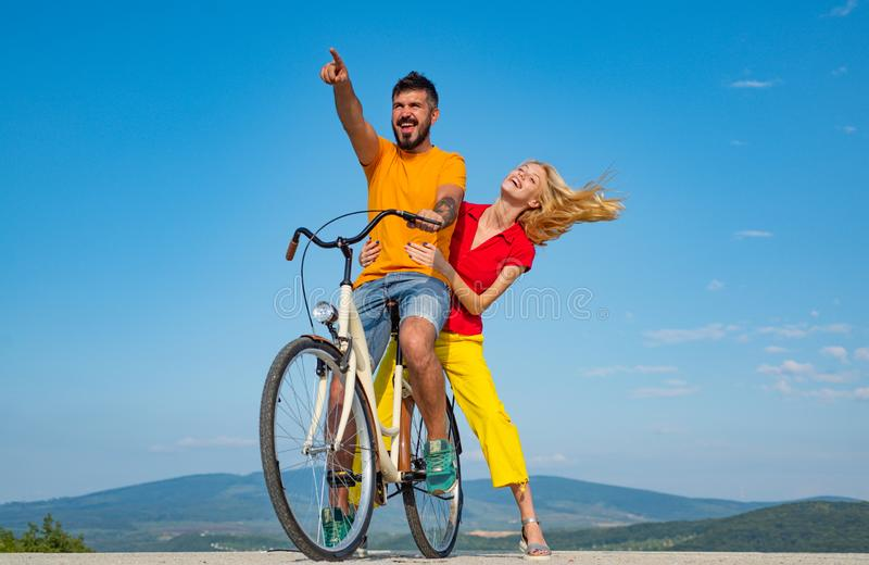 Couple in love riding a bike. Beautiful couple friend adolescents. Relationship. During summer holidays vacation. On the. Clouds of summer love. Summer love royalty free stock images