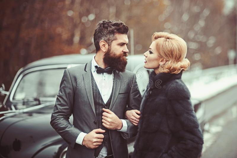 Couple in love on romantic date. Bearded man and sexy woman in fur coat. Retro collection car and auto repair by royalty free stock image