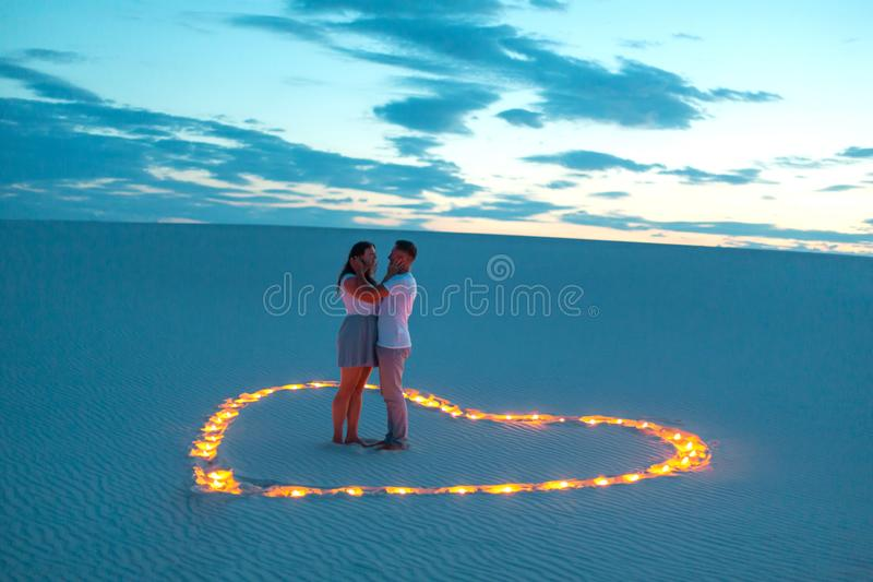 Couple in love romantic hugs in sand desert. Evening, romantic atmosphere, in sand burn candles in form of heart royalty free stock photo